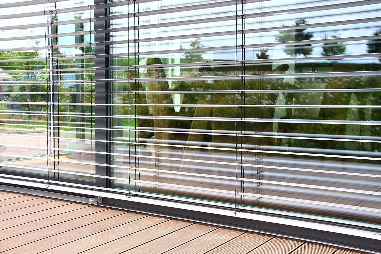 Um ein Überhitzen der Räume im Sommer zu vermeiden sind Jalousien oder Raffstore für bodentiefe Fenster empfehlenswert.