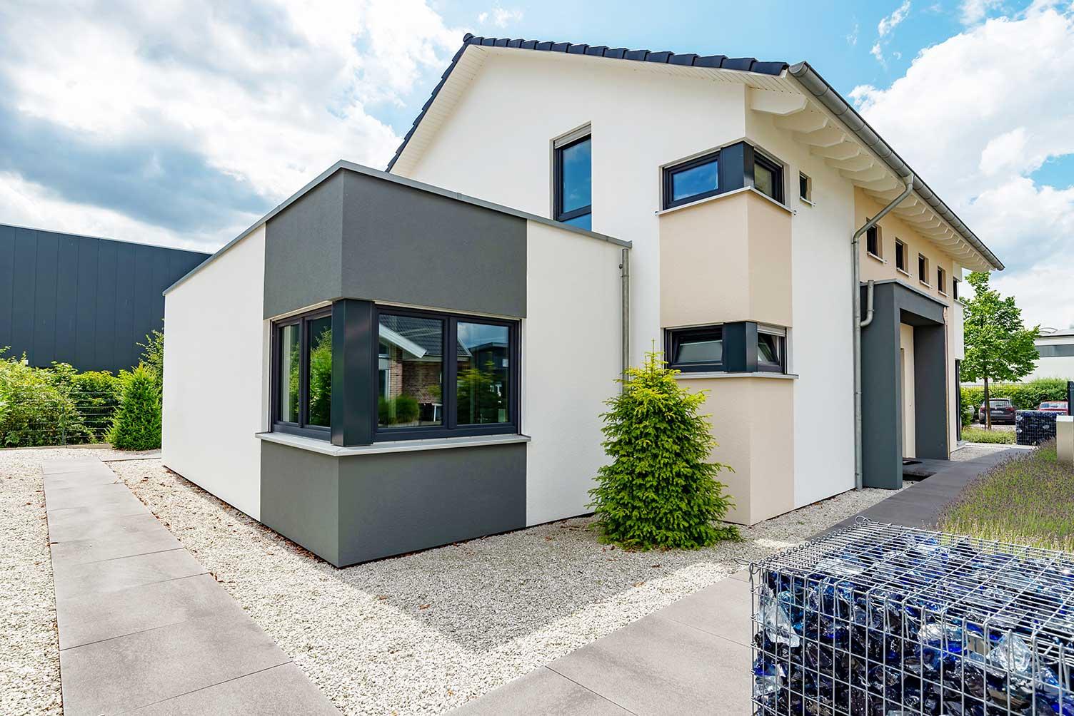 Anthrazitfarbene Fenster lassen die Fassade des Eigenheims im modernen Look erscheinen.
