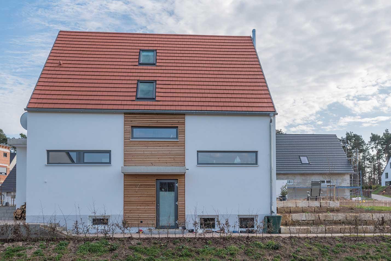 Durch die anthrazitgraue Farbe und die horizontal liegende Form der Fenster wirkt die Fassade des Hauses modern und gradlinig.