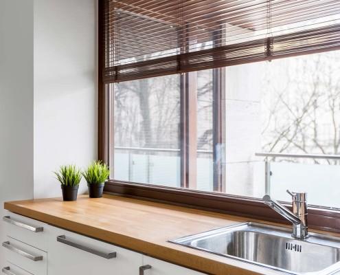 Kunststofffenster in einer dunklen Holzoptik ergänzen eine moderne Küche optimal.