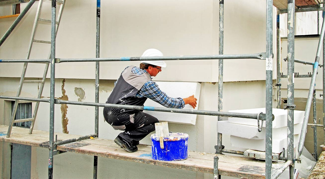 Mann dämmt Gebäudehülle