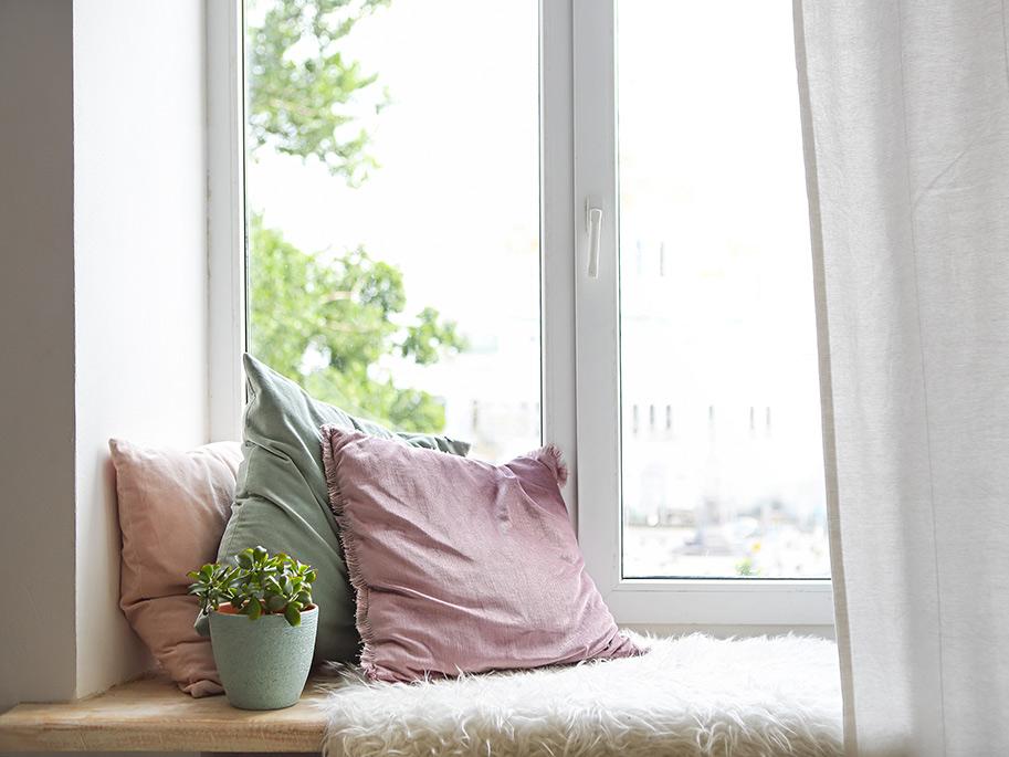 Fensterbank mit Kissen und Decke