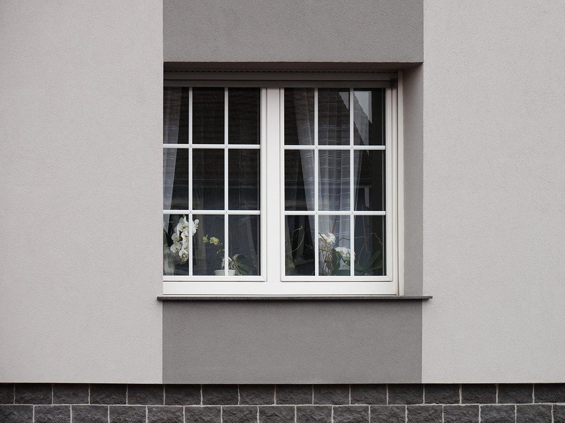 Fenster mit Fensterbank vor grauer Hauswand