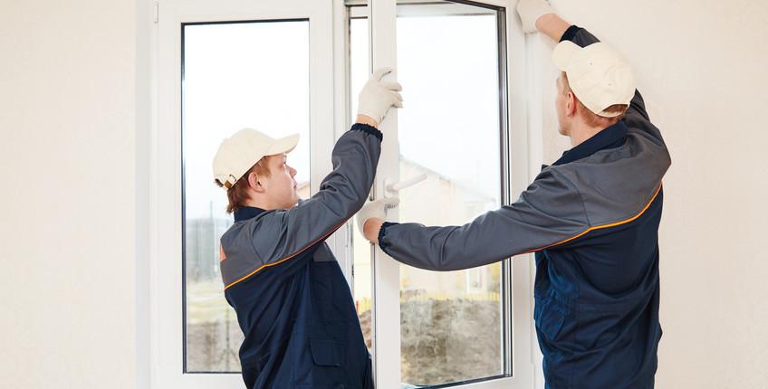 Zwei Handwerker montieren ein Fenster